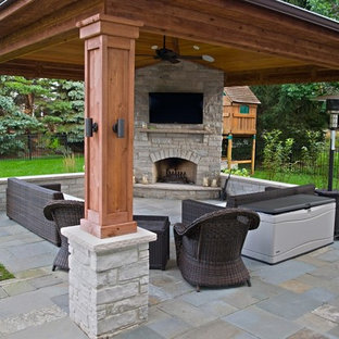 Design ideas for a large back patio in Chicago with an outdoor kitchen, natural stone paving and an awning.