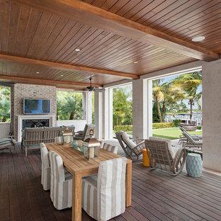 Idee per un patio o portico stile marino di medie dimensioni e dietro casa con un focolare, pedane e un tetto a sbalzo