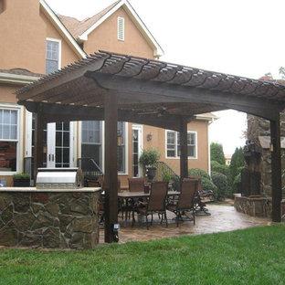Esempio di un grande patio o portico eclettico dietro casa con un caminetto, pavimentazioni in pietra naturale e una pergola