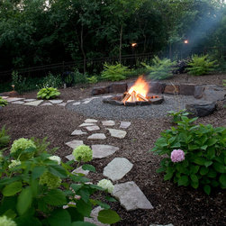 Natural and Fun Backyard - The same stepping stones are used for the path to carry the same theme throughout.  The firepit is surround by boulders for both the appeal and for extra seating.  The clients likes hydrangeas so we used the area around the firepit to plant plenty varieties of the plant.