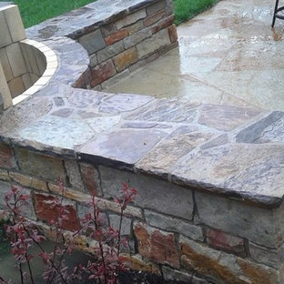 Patio - large tropical backyard stone patio idea in St Louis with a fire pit and an awning