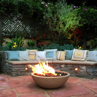 Mid-sized tuscan backyard stone patio photo in Los Angeles with a fire pit