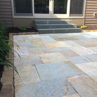 Inspiration for a mid-sized timeless backyard stone patio remodel in Other with no cover