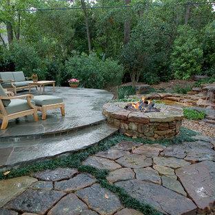 Esempio di un patio o portico tropicale di medie dimensioni e dietro casa con un focolare e pavimentazioni in pietra naturale