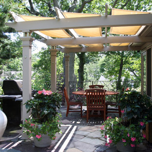 Medium sized eclectic back patio in Boston with an outdoor kitchen, natural stone paving and an awning.