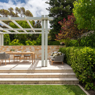 Photo of a large mediterranean backyard patio in Perth with natural stone pavers and a pergola.