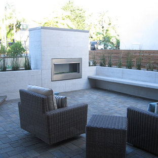 Mid-sized minimalist brick patio photo in San Diego with a fire pit and no cover
