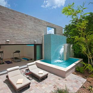 Inspiration för mellanstora moderna uteplatser på baksidan av huset, med en fontän och naturstensplattor