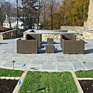 Immagine di un ampio patio o portico tradizionale dietro casa con pavimentazioni in pietra naturale