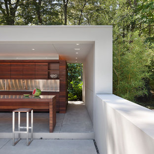 Inspiration for a large modern backyard concrete patio kitchen remodel in New York with a gazebo
