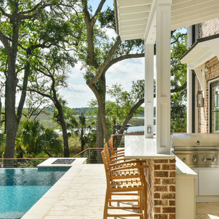 Photo of a large classic courtyard patio in Charleston with an outdoor kitchen, natural stone paving and an awning.