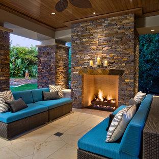 Cette photo montre une grande terrasse arrière tendance avec un foyer extérieur, une extension de toiture et des pavés en pierre naturelle.