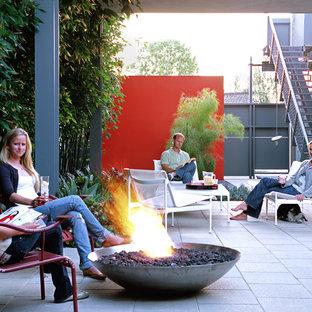 На фото: дворики на внутреннем дворе в стиле модернизм с местом для костра