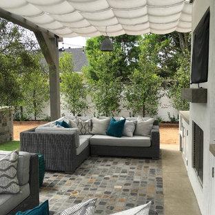 Immagine di un patio o portico stile marinaro di medie dimensioni e dietro casa con pavimentazioni in pietra naturale e un parasole