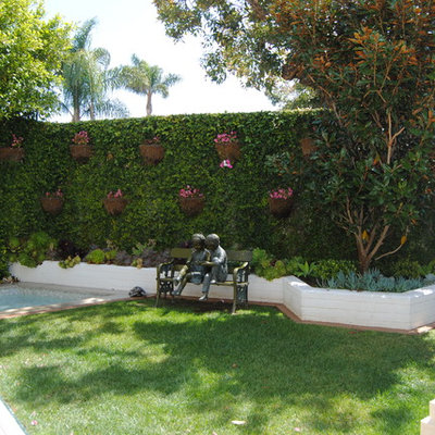 Large elegant backyard concrete paver patio vertical garden photo in Orange County with a roof extension