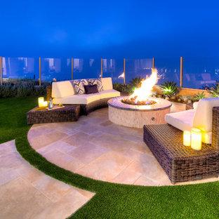 Exemple d'une terrasse et balcon arrière tendance de taille moyenne avec un foyer extérieur et des pavés en pierre naturelle.