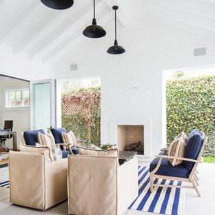Ispirazione per un patio o portico stile marinaro con un tetto a sbalzo, lastre di cemento e un caminetto
