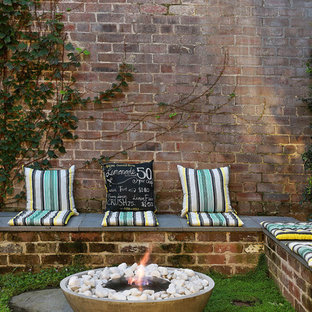 Idee per un patio o portico industriale dietro casa con un focolare