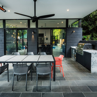 Large contemporary backyard patio in Melbourne with an outdoor kitchen, natural stone pavers and an awning.