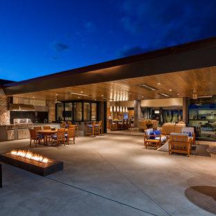 Réalisation d'une terrasse avec une cuisine extérieure arrière design avec une dalle de béton et une extension de toiture.