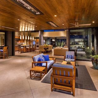 Foto di un grande patio o portico stile americano dietro casa con un caminetto, lastre di cemento e un tetto a sbalzo