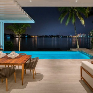 Inspiration for a large contemporary backyard tile patio remodel in Miami with a roof extension