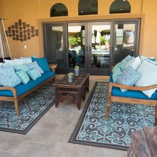 Idee per un ampio patio o portico bohémian dietro casa con piastrelle e un tetto a sbalzo