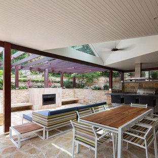 This is an example of a contemporary backyard patio in Sydney with a water feature, natural stone pavers and a roof extension.