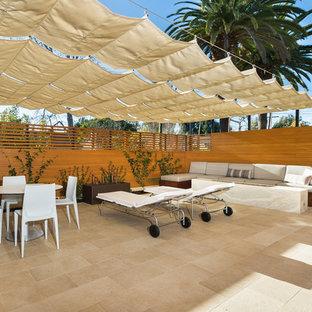 Imagen de patio minimalista, de tamaño medio, con suelo de baldosas y toldo