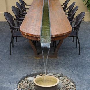 Ispirazione per un patio o portico american style di medie dimensioni e dietro casa con fontane, cemento stampato e una pergola