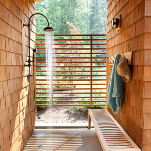На фото: летний душ на заднем дворе в стиле рустика с покрытием из бетонных плит и навесом с