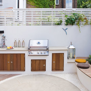 This is an example of a contemporary back patio in London with an outdoor kitchen and no cover.