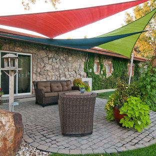 Esempio di un patio o portico bohémian dietro casa con un giardino in vaso, pavimentazioni in cemento e un parasole