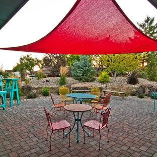 Idee per un patio o portico boho chic dietro casa con un focolare, pavimentazioni in cemento e un parasole