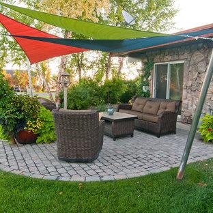 Esempio di un patio o portico boho chic dietro casa con un giardino in vaso, pavimentazioni in cemento e un parasole