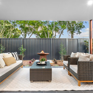 Photo of a contemporary patio in Brisbane with tile and a roof extension.