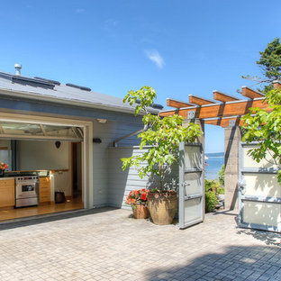 Inspiration for a mid-sized beach style courtyard patio in Seattle with an outdoor kitchen, brick pavers and a pergola.