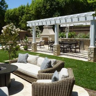 Immagine di un grande patio o portico tradizionale dietro casa con un focolare e pavimentazioni in pietra naturale