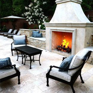 Esempio di un grande patio o portico chic dietro casa con pavimentazioni in pietra naturale e un caminetto