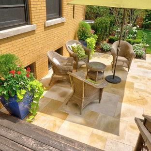 Immagine di un patio o portico vittoriano di medie dimensioni e dietro casa con un giardino in vaso, pavimentazioni in pietra naturale e un parasole