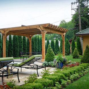 Foto di un patio o portico vittoriano di medie dimensioni e dietro casa con un giardino in vaso, pavimentazioni in pietra naturale e una pergola