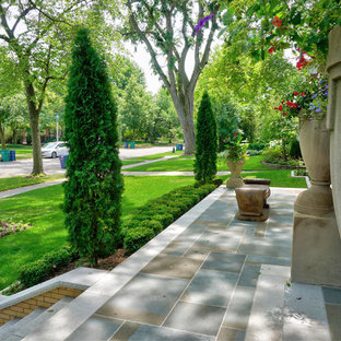 Design ideas for a large victorian front yard patio with a container garden and natural stone pavers.