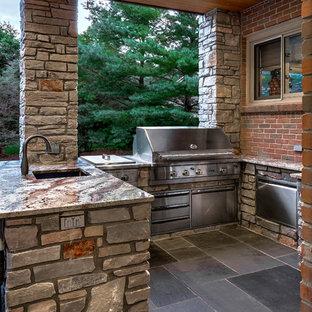 Esempio di un patio o portico design di medie dimensioni e dietro casa con pavimentazioni in pietra naturale e una pergola