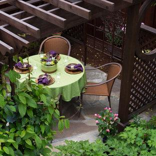 Idee per un patio o portico etnico di medie dimensioni e dietro casa con fontane, pavimentazioni in pietra naturale e una pergola