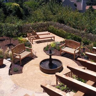 Foto di un grande patio o portico mediterraneo dietro casa con fontane, graniglia di granito e una pergola