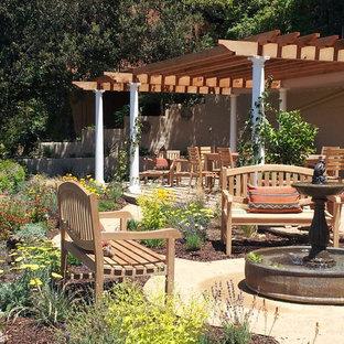 Idee per un grande patio o portico mediterraneo dietro casa con fontane, graniglia di granito e una pergola