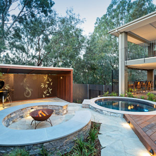 Large contemporary backyard patio in Melbourne with a fire feature and natural stone pavers.
