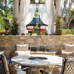 Ejemplo de patio mediterráneo, en patio trasero, con adoquines de piedra natural, fuente y pérgola