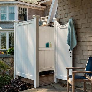 Aménagement d'une grande terrasse avec une douche extérieure arrière bord de mer avec aucune couverture et des pavés en pierre naturelle.