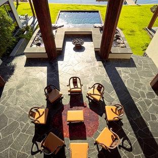Foto di un ampio patio o portico etnico dietro casa con un focolare, pavimentazioni in pietra naturale e un gazebo o capanno